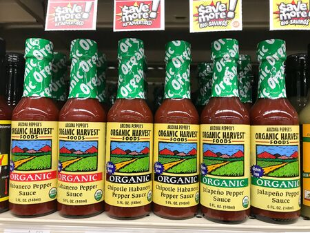 Park City, UT, 1/1/2020: Bottles of various organic spicy sauces stand on a shelf of a supermarket. 免版税图像 - 138056031