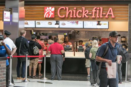 Atlanta, GA 8/28/2019: People are standing in line to a Chick-fil-A cafe at Hartsfield-Jackson Atlanta International Airport. 免版税图像 - 138056034