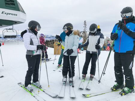 Park City, UT, 12/22/2019: Group of skiers in similar looking outfits stand to have a discussion at Deer Valley resort. 免版税图像 - 138056037