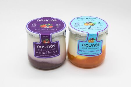 New York, 12/8/2019: Glass containers of Nounos yogurt stand against white background. 免版税图像 - 138056040