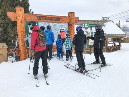 Park City, UT, 12/22/2019: Skiers are checking the Deer Valley resort trail map. 免版税图像 - 138056042
