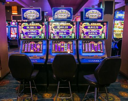Aruba, 11/28/2019: Empty chairs in front of  video slot machines await their patrons inside Stelaris Casino that is a part of Marriott Hotel.