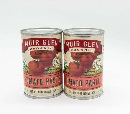New York, 12/8/2019: Two cans of Muir Glen tomato paste stand against white background.