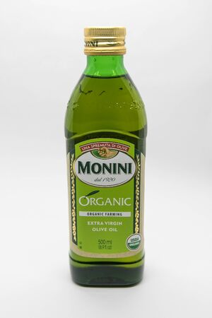 New York, 12/8/2019: Bottle of Monini extra virgin olive oil stands against white background.