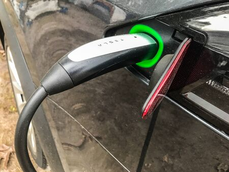 Godeffroy, NY, 09/22/2019: Tesla vehicle is being charged. 免版税图像 - 138056056
