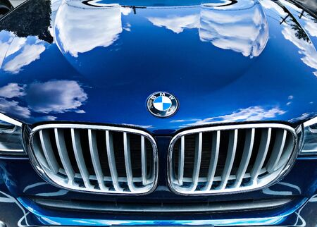 Basking Ridge, NJ, 08/03/2019: Cloudy skies are reflected in a blue BMW's hood.