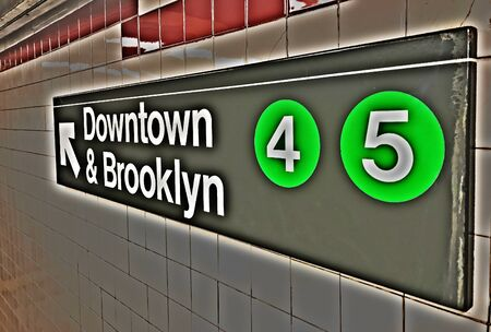 NYC subway sign directing passengers to the platform for trains 4 and 5 running in the direction of Brooklyn. Imagens