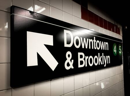 NYC subway sign directing passengers to the platform for trains 4 and 5 running in the direction of Brooklyn. 免版税图像
