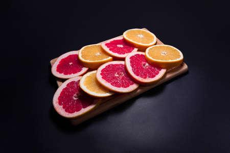 Oranges and red fruit on black wooden boards. Halves of juicy orange on black background. Orange fruit, citrus minimal concept. Top view, copy space