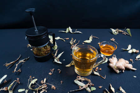 French press and herbal tea, on black background among dry leaves