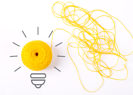 Inspiration concept yarn yellow light bulb metaphor for good idea. Symbol of idea as light bulb on sheet of paper from skein of thread, isolated on white Stock Photo