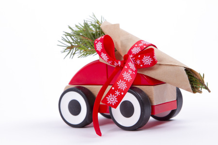 Christmas tree fir branches on toy car. tied with a red ribbon. Christmas holiday celebration concept