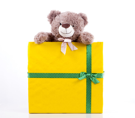 teddy bear in gift box yellow color with a green ribbon with polka dots. peeps. Surprise gift. White background. Stock Photo