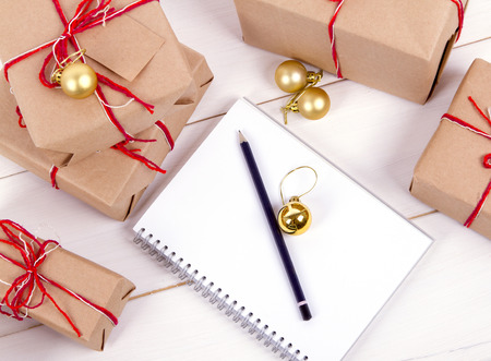 list of gifts for Christmas. Drawing up a list of gifts. presents in kraft paper vintage white wooden background. pencil, notebook Foto de archivo