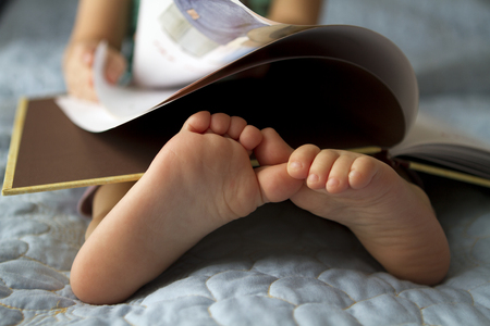 Foot closeup.An image of a toddler reading a book. Stockfoto