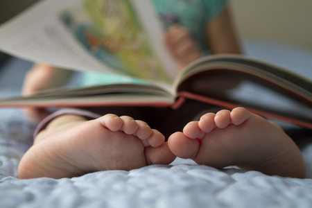 assiduous: Foot closeup. An image of a toddler reading a book at home Stock Photo