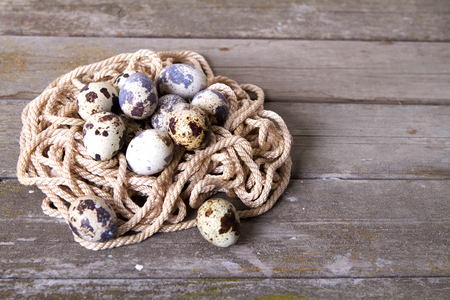 reproduce: quail eggs wood background rope easter