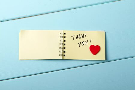 Thank You, A spiral Notepad that has the words Thank You wooden red heart over a distressed wood turquoise background. Valentines Day Stock Photo