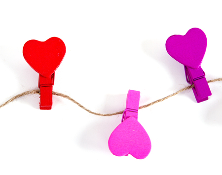 colorful wooden clothespins on a rope Hearts on a white background