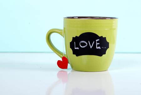 green mug tea bag heart on a blue background. with love inscription Stock Photo