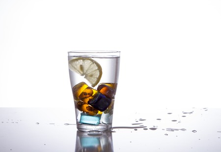glass with multi-colored ice and water splashes