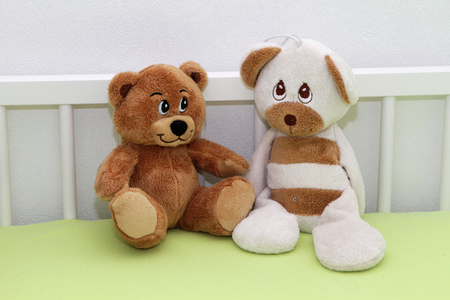 Two teddy bear sitting in the baby cot Stock Photo