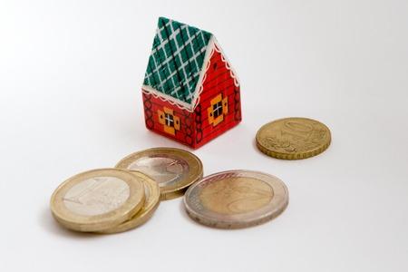 monopolio: Casa roja de juguete de madera y monedas en un fondo blanco.