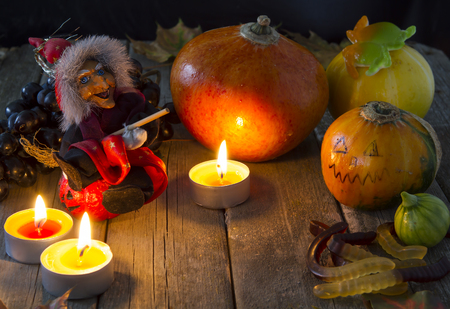 the attributes of Halloween - lit candles pumpkin witch toy gummi worms