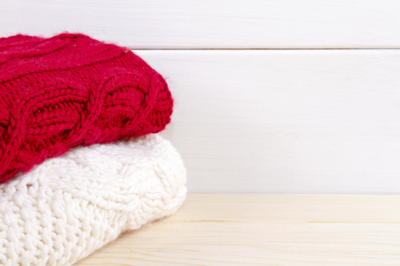 knitwear: stack of clothes from knitted knitwear red and white colour on a  wooden background