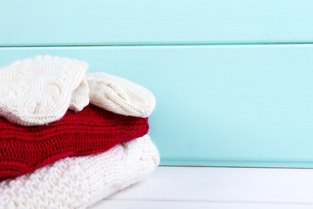 knitwear: stack of clothes from knitted knitwear red and white colour on a turquoise wooden background