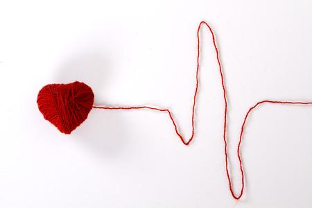 skein of red wool yarn in a heart shape. thread like ECG pattern