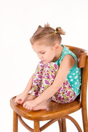 Niño triste está sentado en una silla