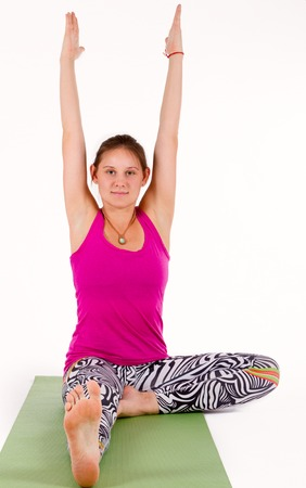 Supple flexible young woman doing exercises working out on a yoga mat, stretching forwards towards her bare foot in the foreground of the view Stock Photo