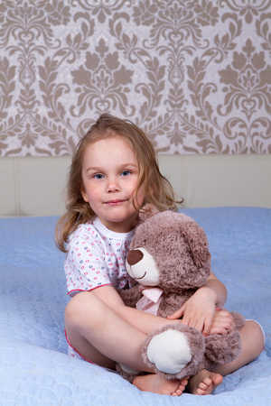 child and toy on the bed