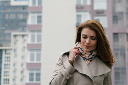 young woman in beige raincoat in the city Stock Photo