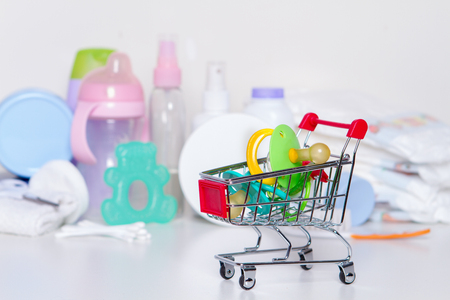 Shopping cart with baby pacifiers with things for baby: purchase for a newborn concept Banco de Imagens - 86364082
