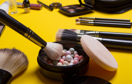 makeup brush and cosmetics, on yellow background isolated flat lay