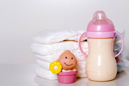 incontinence: New born baby child stack of diapers baby feeding milk bottle with milk on a white background