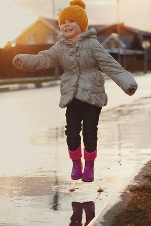 Child jumping in the muddy puddle. closeup of boots Stock Photo