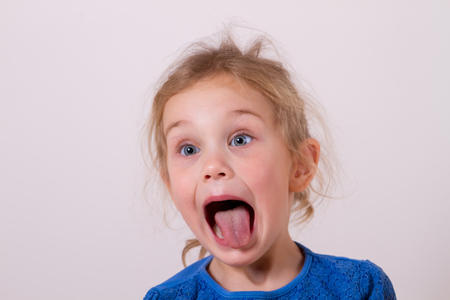smiling little girl shows tongue Stock Photo