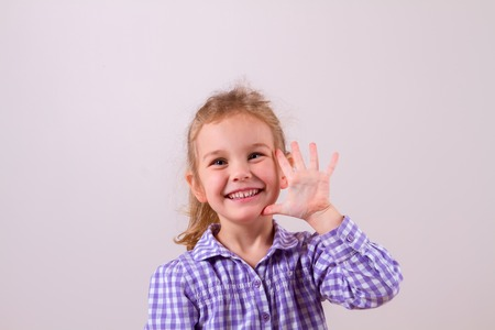Cute little girl happily shows an open hand