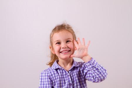 Cute little girl happily shows an open hand