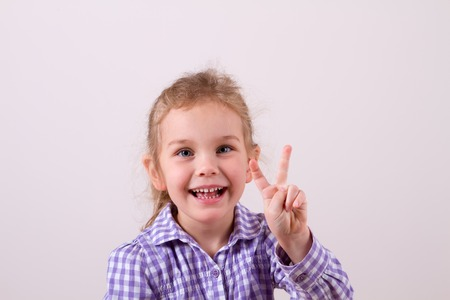 child with a smile shows two fingers