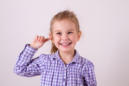 Girl putting finger on her ear Stock Photo