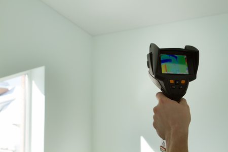 man's hand holds a thermal imager - checks the walls Stock Photo