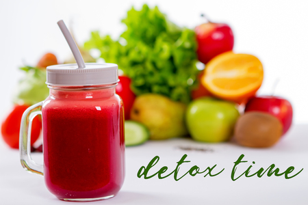 jar of a glass with smoothies from fruits and vegetables. detox time inscription