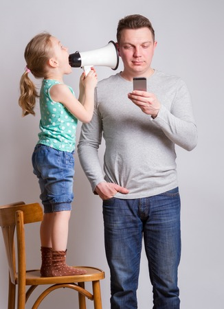 Father using smartphone ignoring his daughter Reklamní fotografie