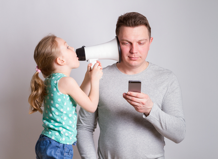 Father using smartphone ignoring his daughter Banque d'images