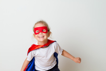 Funny little power super hero child in a red raincoat. Superhero concept.