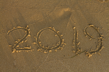 Year 2019 written at the sand on a sea beach.
